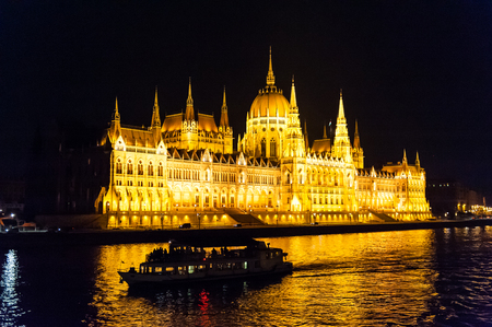 Budapests famous parliament buildings at night, with a silhoutte of a riverboat in front of it.