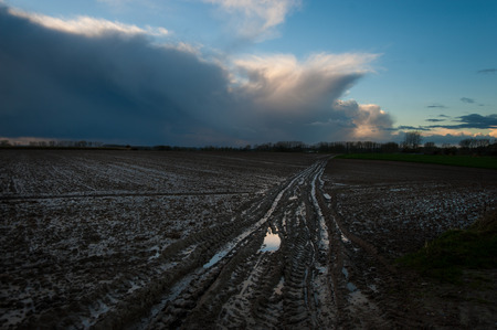 A flooded country road, in the flemish country side, against a clouy sky.
