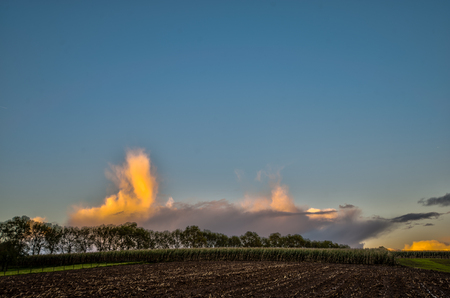 Impressive clouds over a harvested corn field in east flanders Stock Photo