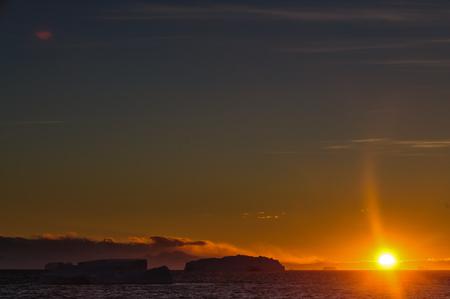Antarktischer Sonnenuntergang: Schwimmende Eisberge im Weddellmeer, nahe der Antarktischen Halbinsel, von einem antarktischen Erkundungsschiff aus gesehen Standard-Bild