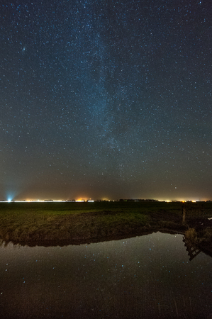 Reflection of the Milky Way Galaxy in a pond of water, in the Frisian countryside