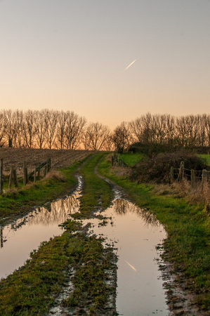 A contrail reflected in a trail running through a rural area in east flanders.