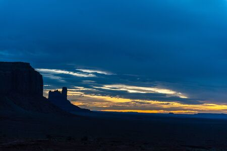 Early morning light of dawn, contasted against the black mesa walls of monument valley.