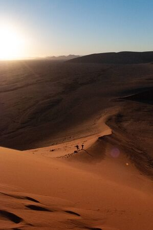 People walking down Dune 45 in the early morning sunlight.