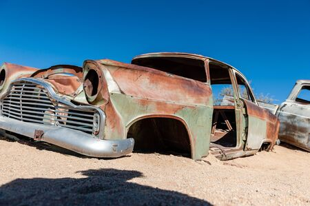 Wrecks of historic cars line the road in the town of Solitaire in the Khomas Region of Namibia.