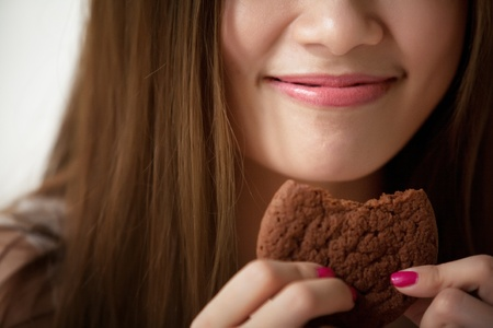Lips Asian girl is eating cookies  Stock Photo