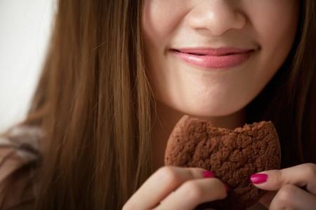 Lips Asian girl is eating cookies  Фото со стока
