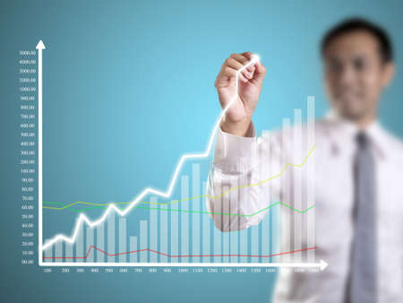 Business man hand drawing a graph Stock Photo - 23576911