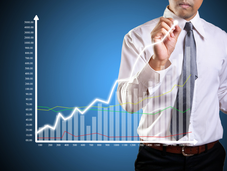 Business man hand drawing a graph Stock Photo - 23576913