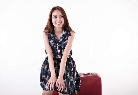 young woman sitting on her travel bag looking faraway isolated on white background