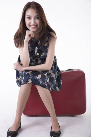 casual woman  sitting on a travel suitcase - isolated on white background photo