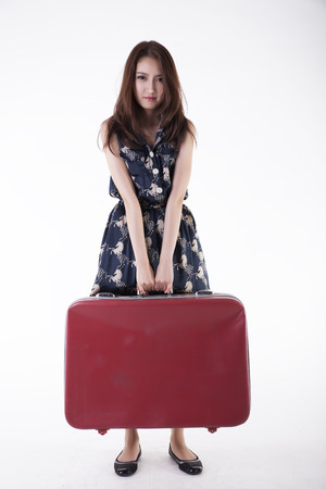 portrait of a beautiful girl with long and developing hair with a suitcase in his hand on a white background Stock Photo