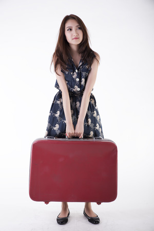 portrait of a beautiful girl with long and developing hair with a suitcase in his hand on a white background photo