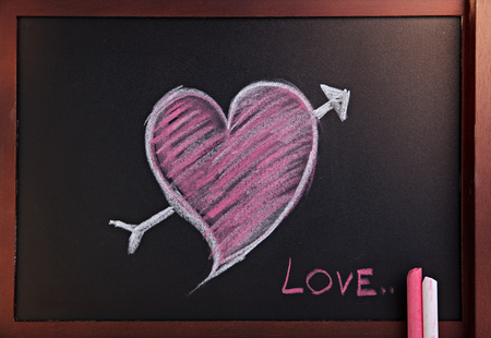 Heart written with chalk on a blackboard  photo
