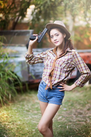 Asian woman wearing a cowboy hat and holding a gun  photo