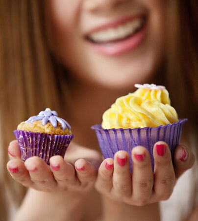 Asian woman holding cupcakes big and small.