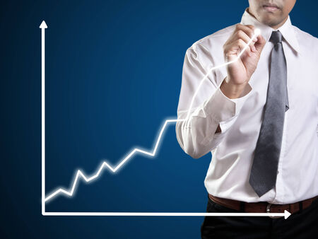 Business man hand drawing a graph photo