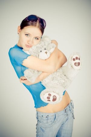 Beautiful blonde teenager holding a teddy bear photo