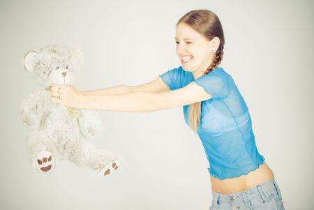 throttle: Beautiful blonde teenage girl throttle a teddy bear Stock Photo