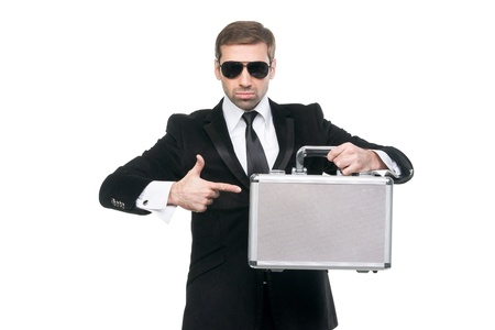 Stylish securuty guard pointing his finger on a metal suitcase. Isolated over white background photo