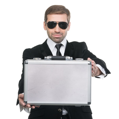 Stylish securuty guard presenting a metal suitcase. Isolated over white background photo