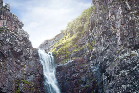 Waterfall falling from high rocks in Fulufjallet Nature Reserve
