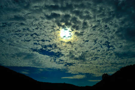 the photographer's view of the summer sky with the sun and broken clouds evoking the emotions of romance Stock fotó
