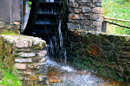 photo of water splinters from a rotating wooden water wheel in a mill drive driving a gold ore mill Stock Photo