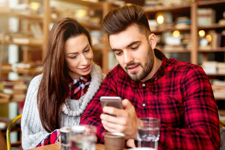 Hipster couple at restaurant looking at smart phone.