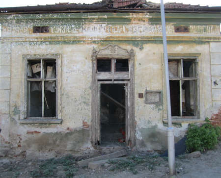 without windows: Entrance into abandoned and ruined city house with tall ornamental doors and windows without glass and broken roof Stock Photo