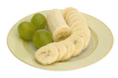 grapes and banana sliced on plate