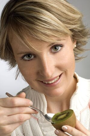young woman eating kiwi Stock Photo - 593563