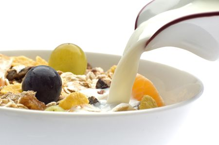 milk pouring in a bowl of muesli with grapes photo