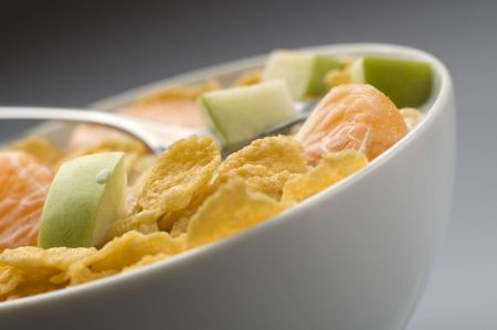 bowl of yellow cornflakes with fruit close up