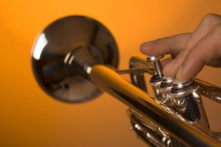 fanfare: trumpet playing on orange bacground close up