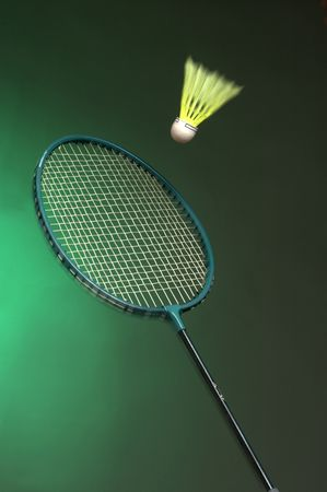 double game: badminton racket and shuttle on green background close up