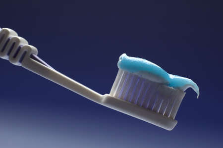 tooth brush in blue cup close up photo