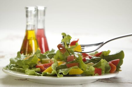 lettuces: fresh colorful salad close up on the table with oil and winegar
