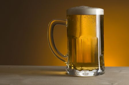 glass of beer on orange background close up photo