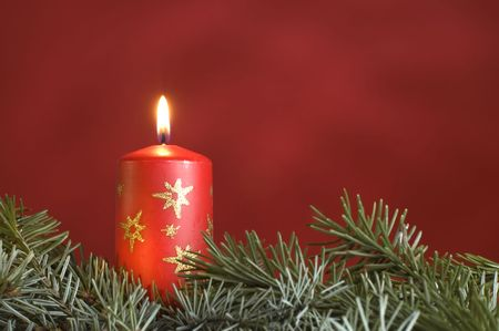 red candle with branch infront and red background Stock Photo - 616102