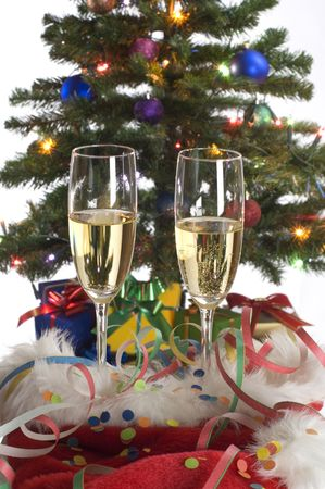 two glasses of champagne close in front of christmas tree