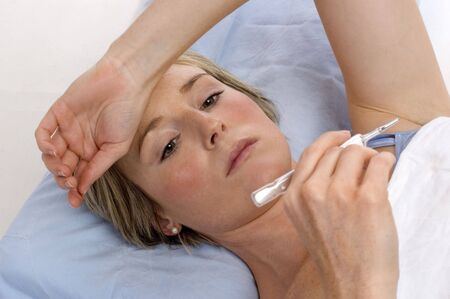 young woman in bed checking temperature on thermometer Stock Photo