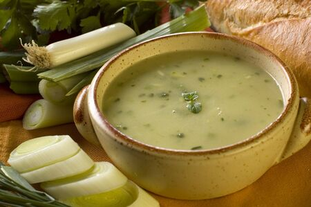 leek soup decorated with fresh vegetables and bread photo