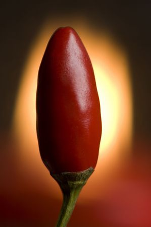 capsaicin: Red hot chilli pepper with fire in background close up   Stock Photo