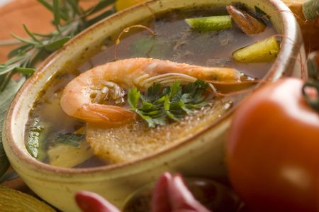 l plate: prawn sea food soup with tomato close up