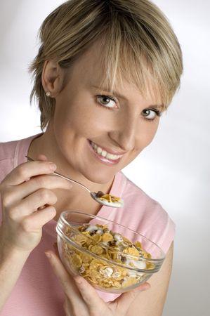 young woman eating corn flakes close up
