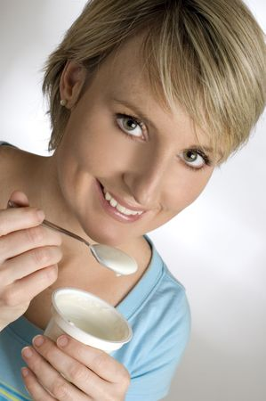 young blondie woman eating yogurt close up