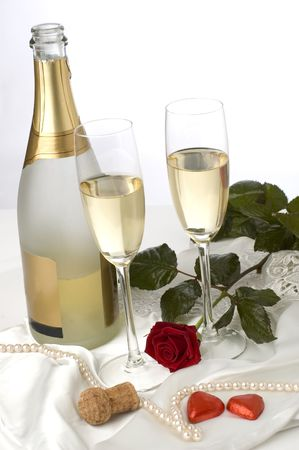 bottle of champagne with two glasses, rose and candy