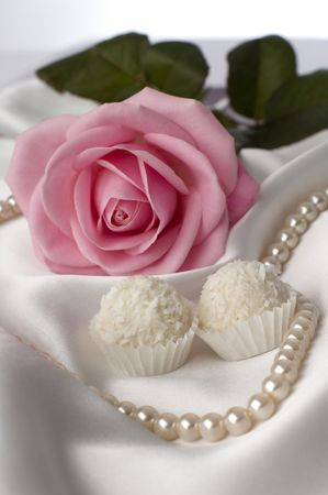 pink rose with white candy in front on silk close up photo