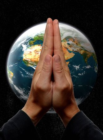 praying hands in front of earth concept Stock Photo